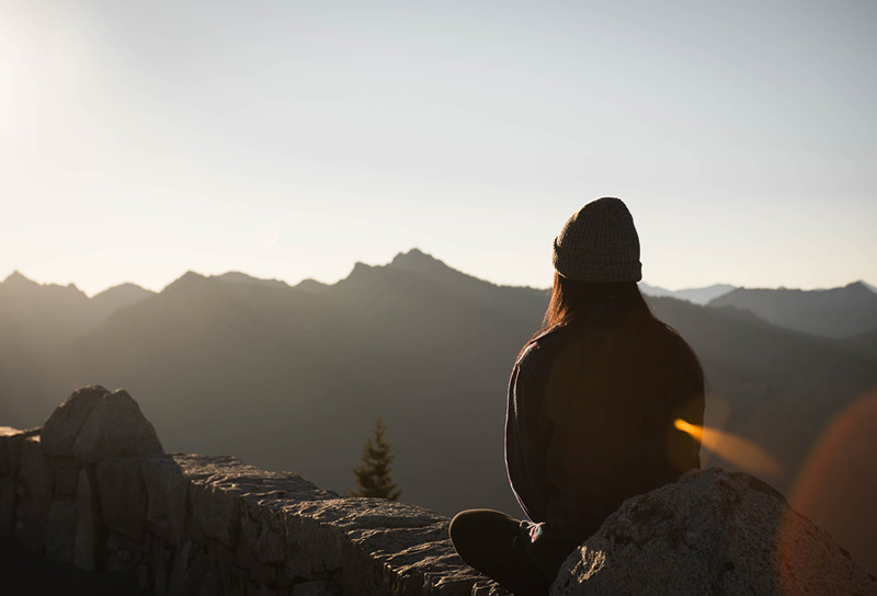 γυναίκα καθισμένη σε ένα βράχο σκέφτεται τον Κορωνoϊό ως μια ευκαιρία προσωπικής ανάπτυξης
