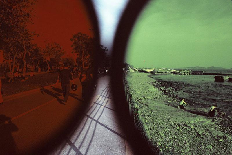 ένας πράσινος φακός που δείχνει έναν δρόμο με κόσμο και ένας κόκκινος που δείχνει μία παραλία