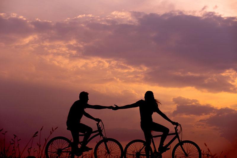 γυναίκα και άντρας πάνω σε ποδήλατα που πιάνουν τα χέρια τους