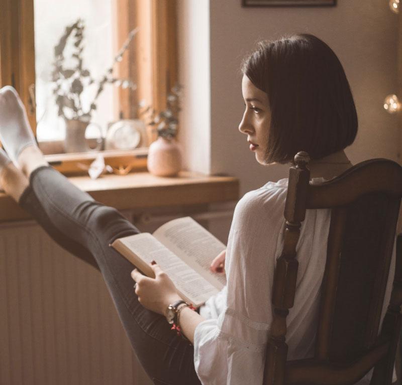 γυναίκα μέσα στη μοναξιά και τη σύνδεση διαβάζει βιβλίο στον καιρό της πανδημίας