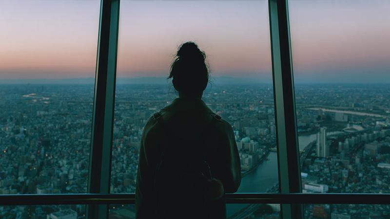 γυναίκα κοιτάζει έξω από το παράθυρο σε μια πόλη