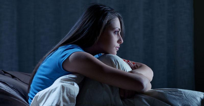 γυναίκα καθισμένη σε κρεβάτι