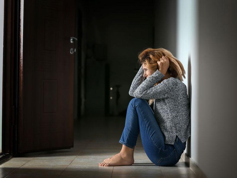 μία κοπέλα κάθεται στο πάτωμα αγχωμένη και κρατάει τα μαλλιά της