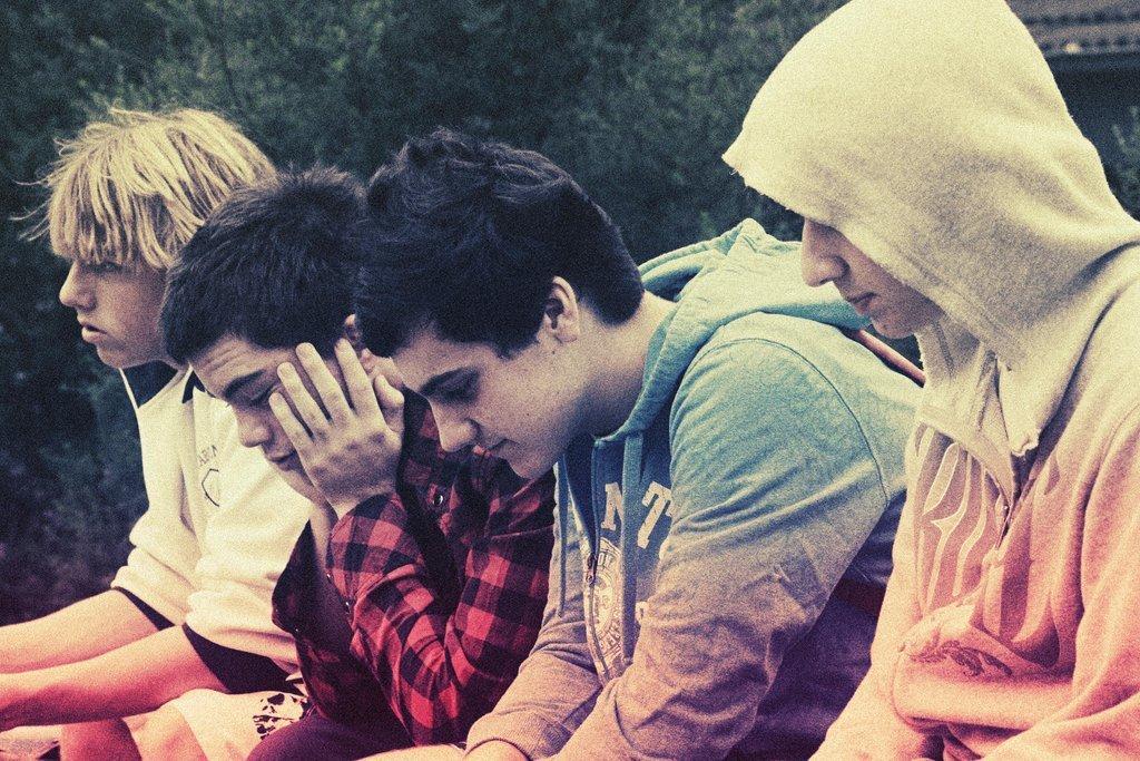 τέσσερις έφηβοι καθισμένοι ο ένας δίπλα στον άλλον και κοιτάζουν κάτω
