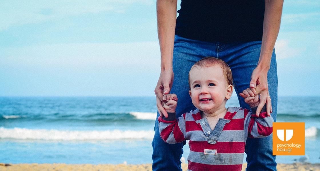 215da3865bb μωρό που χαμογελάει καθώς το κρατάει ο πατέρας του σε μία παραλία με φόντο  τη θάλασσα