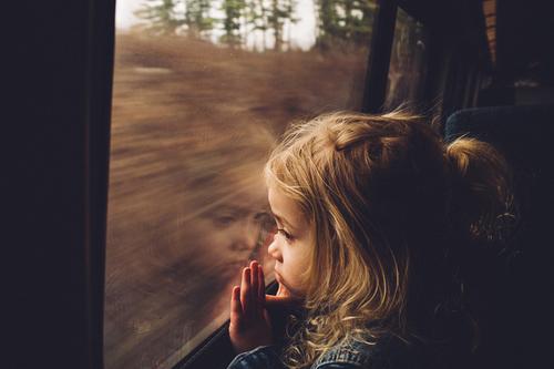 κοριτσάκι κοιτάζει έξω από το παράθυρο ενός τρένου και προσπαθεί να ξεπεράσει τα τραύματα του
