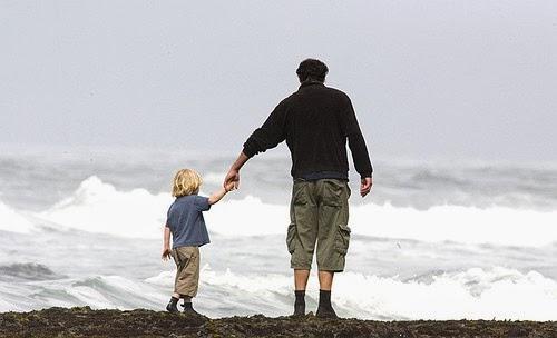 πατέρας κρατά το παιδί του, που ήταν θύμα κακοποίησης, στην παραλία