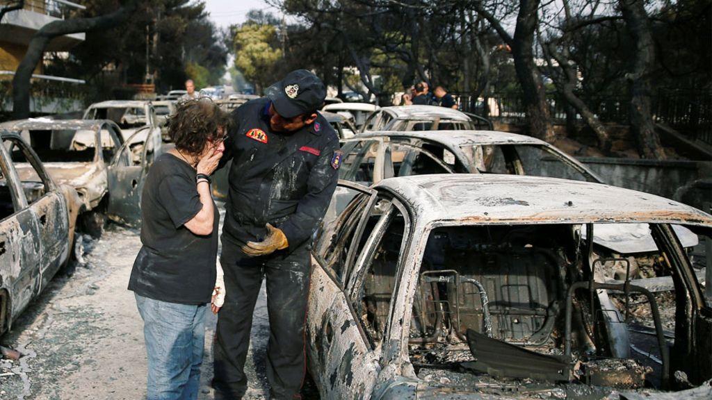 γυναίκα που κλαίει στον ώμο ενός πυροσβέστη κοιτάζοντας μία το καμένο αμάξι της μετά από πυρκαγιά
